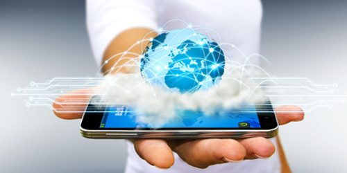 World over a cloud connected to businessman fingers